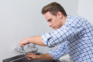 Serious plumber fixing water tap with pliers