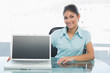 Elegant businesswoman displaying laptop on desk in office