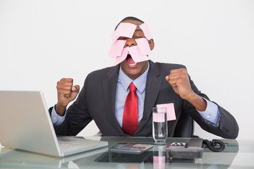 Frustrated Afro businessman with blank notes on face and laptop