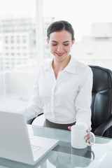 Businesswoman with coffee cup while using laptop at desk