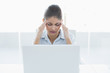 Businesswoman suffering from headache with laptop at office
