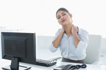 Businesswoman with neck pain in front of computer