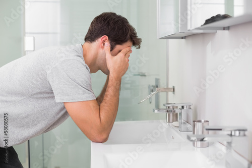 Young man with head in hands at washbasin
