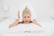 Angry woman covering ears with pillow in bed