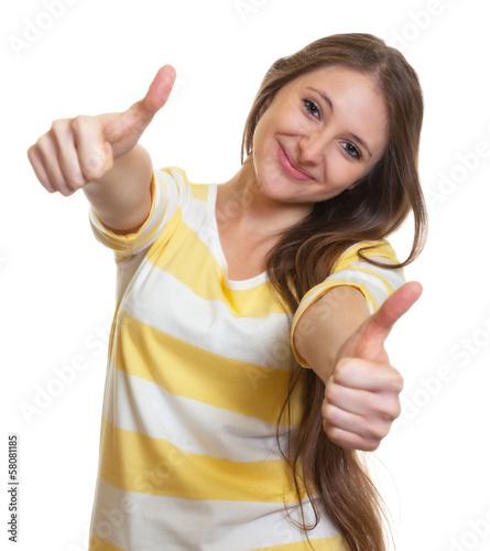 Lachende Frau mit langen Haaren zeigt beide Daumen
