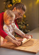 Mother and baby rolling pin dough in christmas decorated kitchen