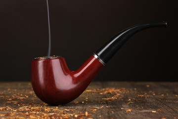 Smoking pipe and tobacco on wooden table on black background