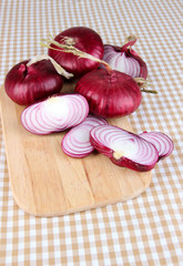 Fresh red onions on table