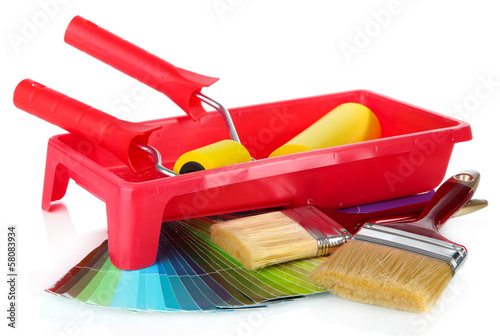 Roller, brushes and bright palette of colors isolated on white