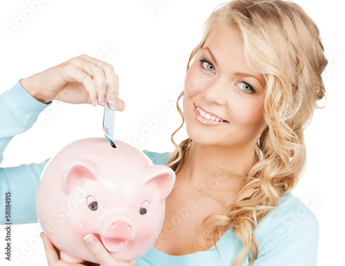 woman puts cash money into big piggy bank