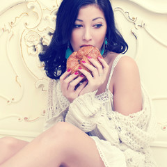 Young beautiful woman eating her french croissant