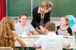 Lehrer und Schüler bei Gruppenarbeit in Schule