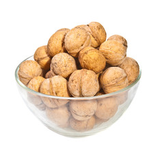 walnuts in a glass dish on a white background