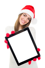 Happy young woman with Santa hat showing tablet computer