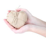 Woman hands holding a heart wrapped in brown kraft paper,