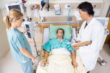 Doctor And Nurse Examining Critical Patient
