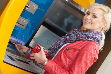 Beautiful smiling woman using an bank ATM