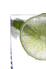 Detail of sliced lime in glass of water, on white background