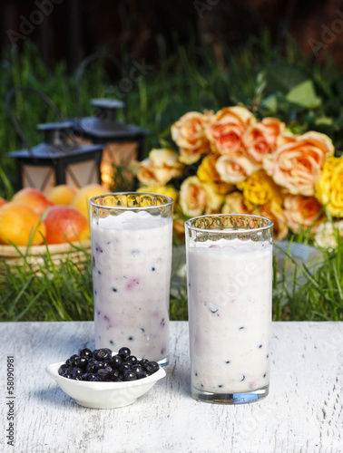Blueberry smoothie on wooden table. Summer party, flowers