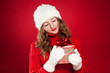 brunette girl holding Christmas present wearing hat and mittens