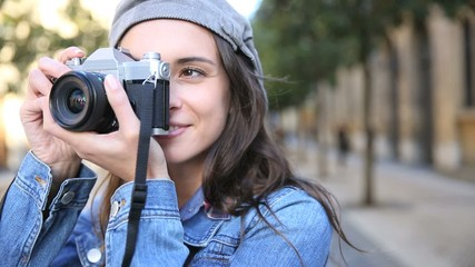 Portrait of trendy girl holding camera