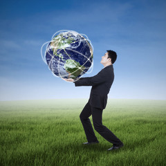 Businessman carrying a globe