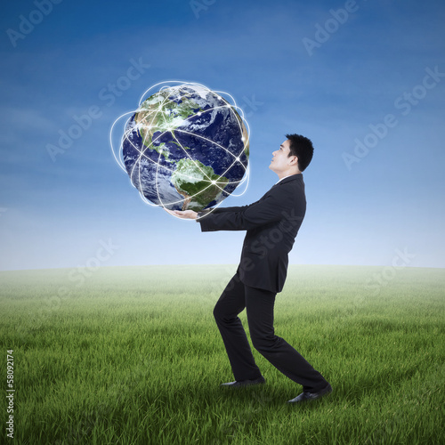 Businessman carrying a globe