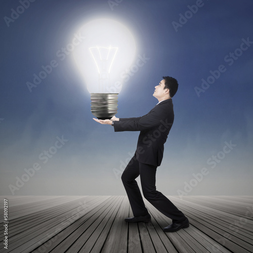 Businessman carrying light bulb