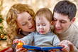 Family at christmas tree. Parents read book to kid.