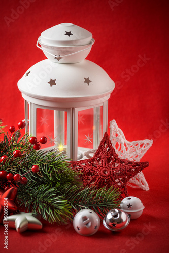 Christmas white lantern is standing with a burning candle in it