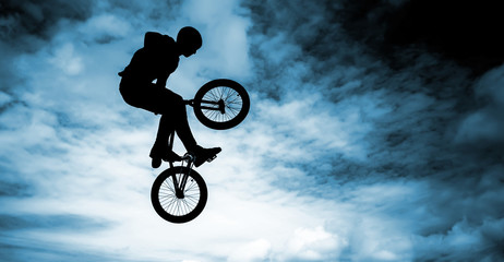 Man doing an jump with a bmx bike over blue sky background.