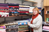 woman  chooses tissue at  fabric store