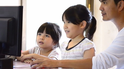 Asian Father And Cute Daughter Playing Computer