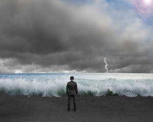 Businessman standing toward waves and cludy sky with Lightning ,