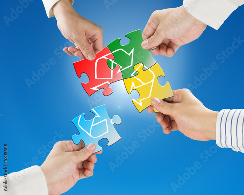 Hands hold puzzles with recycle symbol in blue sky and sunlight