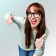 Lachende junge Frau mit schwarzer Brille zeigt Daumen nach oben