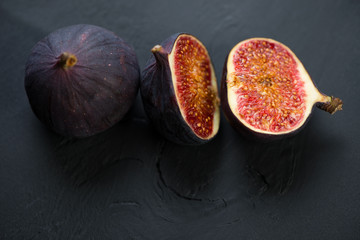Whole and halved fig fruits, black background, view from above