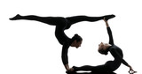 two women contortionist  exercising gymnastic yoga silhouette - 58100359