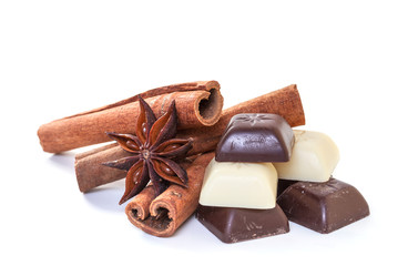 Cinnamon sticks and chocolate on a white background.