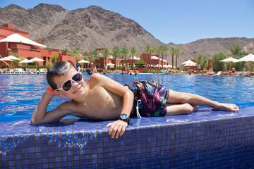 Jeune garçon posant au bord de la piscine