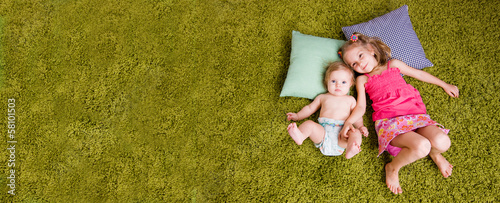 Two happy sisters lie on carpet