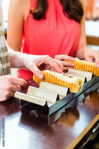 Kunden essen Hotdog in Fast Food Imbiss
