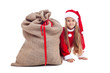 Little girl in christmas outfit hiding behind santa bag