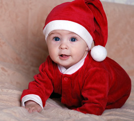 beautiful baby in the hat of Santa Claus with gifts