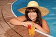 Frau mit Sonnenhut und Getränk erfrischt sich im Pool