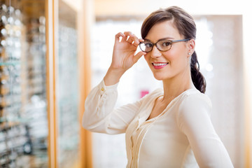 Woman Trying New Glasses In Optician Store