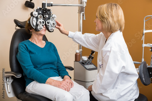 Optician Using Phoropter To Examine Woman's Eyes