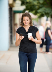 Woman With Coffee Cup Using Smartphone On Pavement