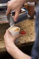 Barista Making Design On Cappuccino In Coffeeshop