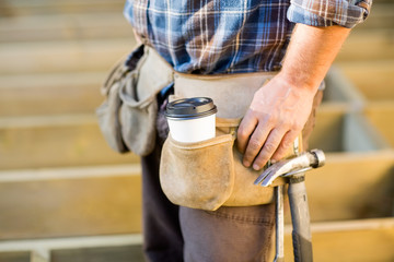 Disposable Coffee Cup And Hammer On Carpenter's Tool Belt